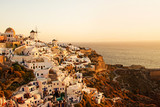 Two white old windmills on a background of white plastered houses at sunset in the town of Oia on Santorini island in Greece