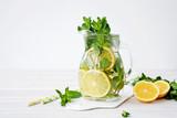 Lemonade in glass jug on light background. Lemon, Mint and Ice Ingredients