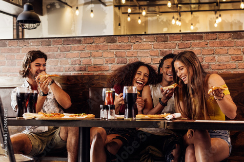 Foto Murales Group of friends having pizza at restaurant