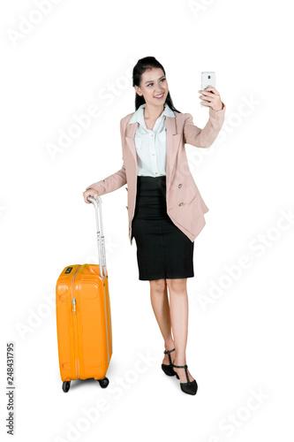 Leinwandbild Motiv Beautiful businesswoman takes photo with luggage