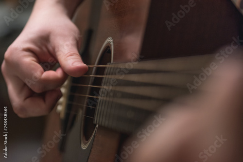 hands playing acoustic guitar - 248438564