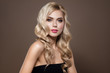 Attractive woman. Blonde haired model Portrait with blue eyes and Healthy Long Shiny Wavy hairtyle. Volume shampoo. Blond Curly permed Hair and bright makeup.  Beauty salon and haircare concept.
