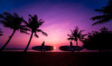Silhouette of surfers couple holding long surf boards at sunset on tropical beach - 248449544