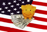 Piggy bank with united states dollar on star-spangled banner - 248449915