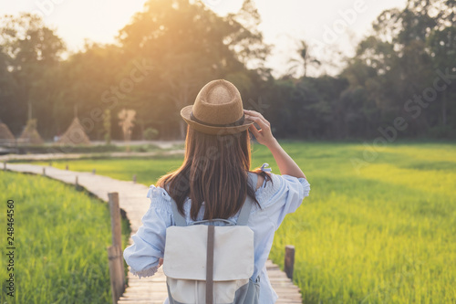 Leinwanddruck Bild Young woman traveler looking at beautiful green paddy field