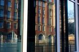 altes Gebäude am Alsterfleet spiegelt sich in Fenstern - 248475314