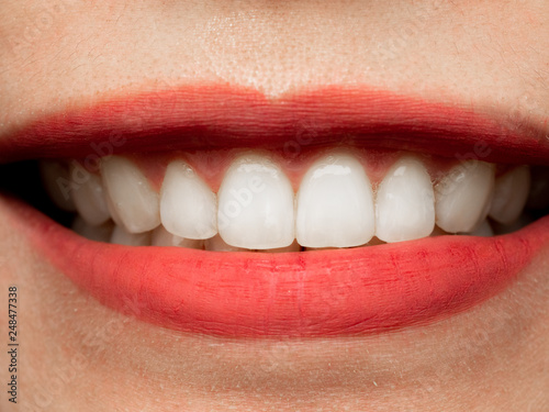 Closeup shot of human Asian Chinese Thai woman female makeup face. Woman with red lips lipstick and healthy dental white great perfect teeth. Smiling, Dental dentist clinic concept.