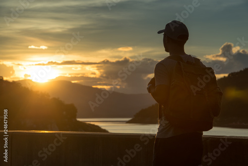 Foto Murales Image of sunrise with a silhouette of a tourist man in natural surrounding