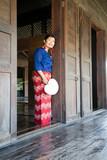 Femme Thaïe habit traditionnel se cachant derrière son éventail en paille tréssée