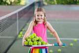 Child playing tennis on outdoor court.