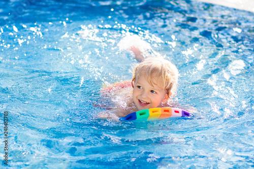 Leinwandbild Motiv Child learning to swim. Kids in swimming pool.