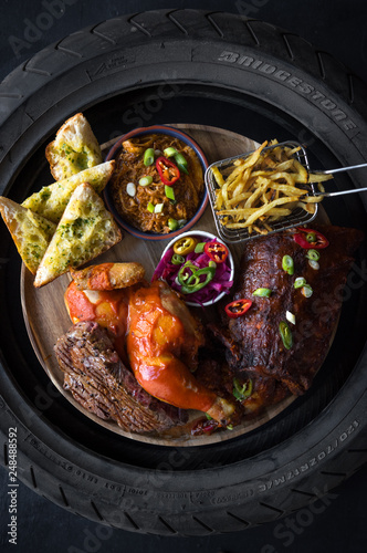 london, england, 05/05/2018 A beautiful delicious golden rack of meaty bbq pork ribs, bbq chicken thigh, french fries in a metal frying basket, , chilli and salad, served in a race tyre.