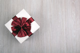 white gift box with a bow on a gray wooden background