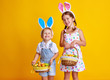 funny happy child boy with easter eggs and bunny ears on yellow