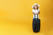 Little child girl blonde is ready for travel and stands with a suitcase. Yellow background