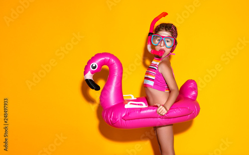 obraz PCV happy child girl in swimsuit with swimming ring flamingo on colored yellow background