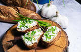 French Baguette with white curd spread decorated with green fresh chive served on wooden plate