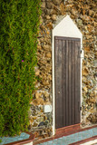An old door on a wall with sea rocks on the sea walk in Castiglioncello in Tuscany