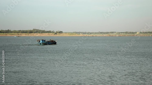 dredging boat proceeding down river to pump sand