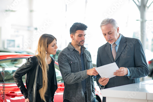 Happy young family talking to the salesman in a car showroom - 248506703