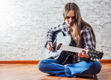 young teenager brunette girl with long hair sitting on the floor and playing an black acoustic guitar on gray wall background