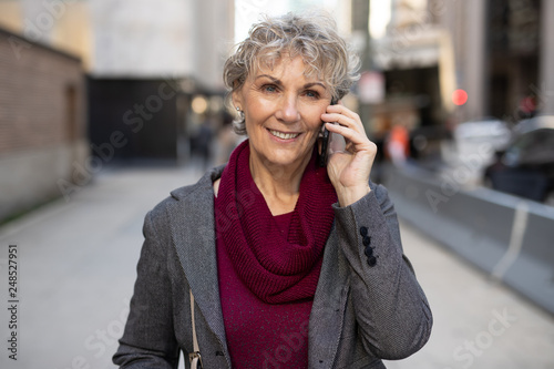 Mature woman in city walking talking on cell phone