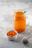 Colorful hot sea buckthorn tea with rosemary and fresh sea buckthorn berries on a grey table. Vitamin drink.