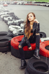Gorgeous beauty model posing outdoors in street racing with tires and cars on background. Speed, sport, beauty concept