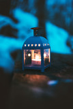 Lamp with candle on a wood. Winter dark background. Old lantern with candle in a nature.  - 248536949