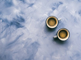 Two coffee cups on sky blue painted background