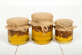 Almond nuts with honey in glass jars on white wooden boards.