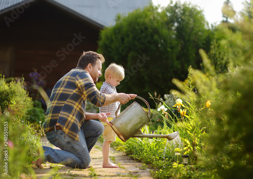 Middle age man and his little son watering flowers in the garden at summer sunny day.