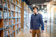 Asian man university student holding book near bookshelves in college library for education research. Bestseller collection in bookstore. Scholarship or educational opportunity concepts