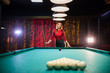 Billiard club. A woman with red hair standing by the table