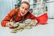 Leinwanddruck Bild - surprised repairman in uniform lying on floor near money in office