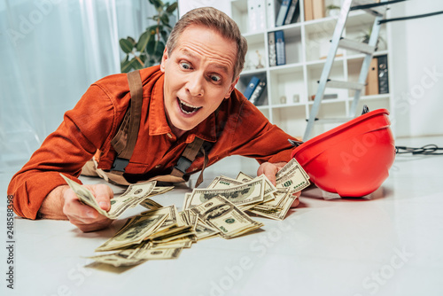 Leinwanddruck Bild surprised repairman in uniform lying on floor near money in office