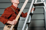 cropped view of repairman in orange uniform climbing with wooden board in hand on ladder in garage