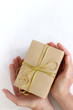 gift giving. box with a bow in hands over a light surface top view