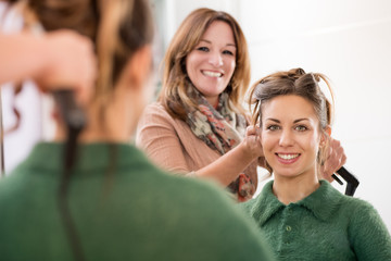 Smiling happy faces of a hairstylist and client