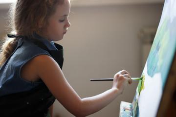 Preschool girl painting in art class. Close up photo brush in hand