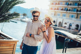 Happy young couple walking by the harbor of a touristic sea resort with sailboats on background - 248600593