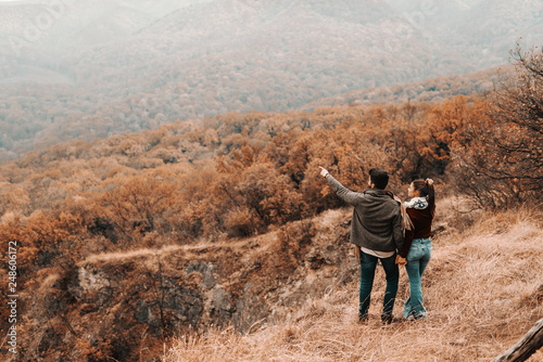 Happy couple holding hands and looking at beautiful view. Man pointing at something. Autumn time, backs turned. - 248606172