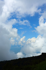 fluffy mist cloud on sky above evergreen mountain of green jungle woods © sutichak