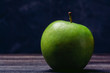 Beautiful ripe green apple close-up on a dark background