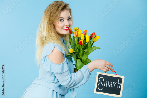 Woman holds tulips, board with text 8 march