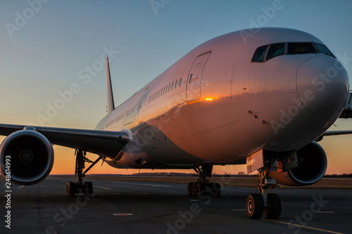 White wide body passenger aircraft at the airport apron in the evening sun