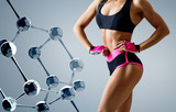 Athletic woman standing near glass molecule chain.