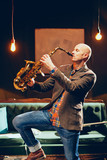 Portrait of bald saxophonist playing his instrument in home studio.