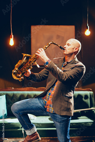 Portrait of bald saxophonist playing his instrument in home studio. - 248616756