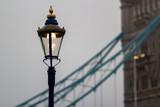 Street lantern against the Tower bridge in deep morning fog. London, the UK
